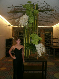 Jaclyn standing in front of a floral art design at Symposium