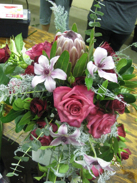 Sanaa+ Roses from Eufloria paired with Dr. Rupple Clematis from Roseville Farms, accented with Fabulous Foliage from FernTrust and Resendiz Mink Protea!