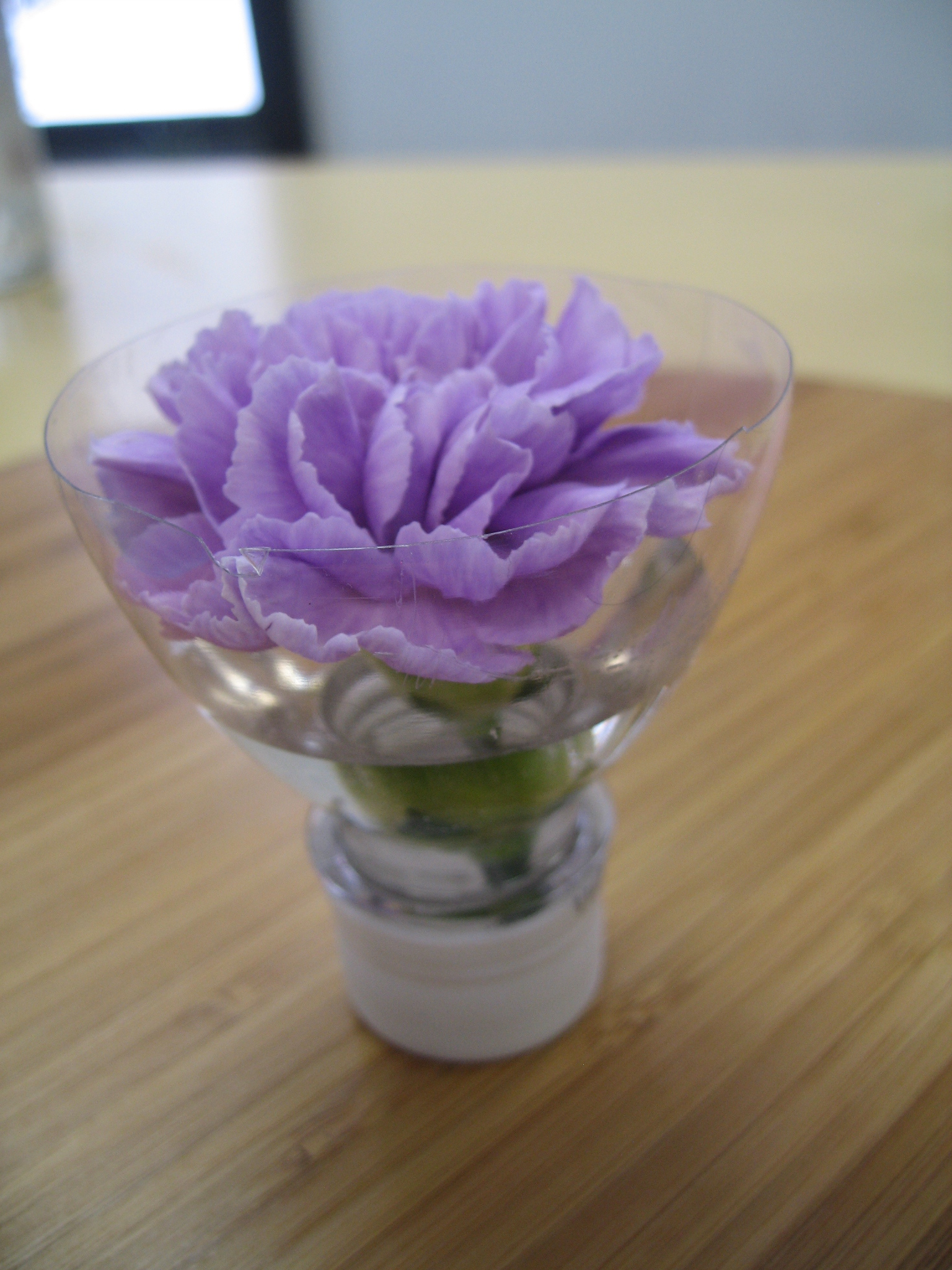 From a simple water bottle you can create this fun vase for a single flower!