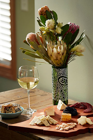Re-purposing a Protea Wine Bottle into a vase to accompany the cheese tray!