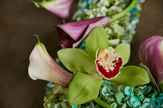 J uses decorative corsage pins to attach the orchids and callas to the wreath!