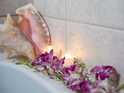Orchid blooms and candles help create a more relaxing atmosphere to accompany your bath!