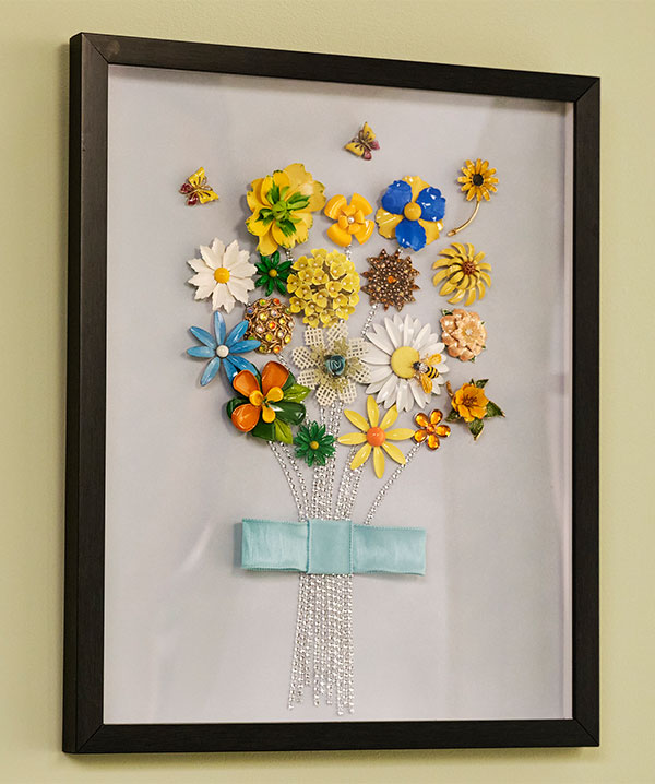 This is a super fun way to repurpose beautiful flower brooches- into a lovely work of art you can hang in your home!