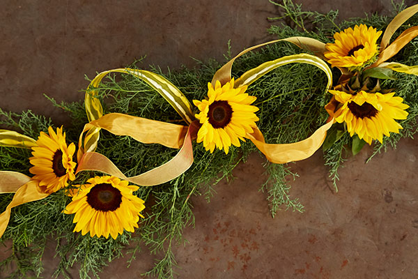 Here's a quick decoration- you can create with a garland (even a Christmas Garland) and a few Sunflowers and ribbon... it's Simple and FUN!